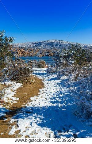 A Snowy Trail Through The Desert Leading To Watson Lake In Prescott Arizona.