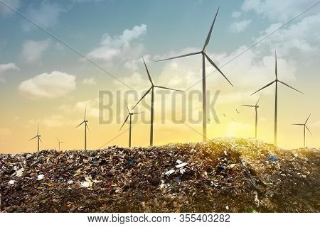View Of A Wind Turbines On Top Of Garbage Mountains, Dramatic Sunset Sky. Green Energy Concept.
