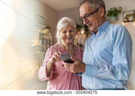 Senior couple looking at a smartphone together at home