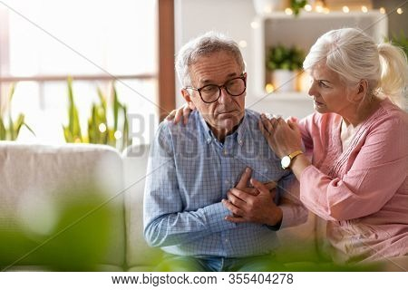 Senior woman helping her husband with chest pain