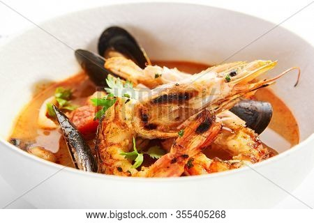 Tom Yum with seafood in bowl. Served main course close up. Thai sour and spicy soup with shrimp and mussels. Restaurant Asian traditional food. Dinner, Thailand gourmet meal in plate