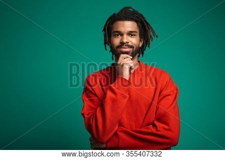 Portrait of pleased african american man smiling and looking at camera isolated over green background