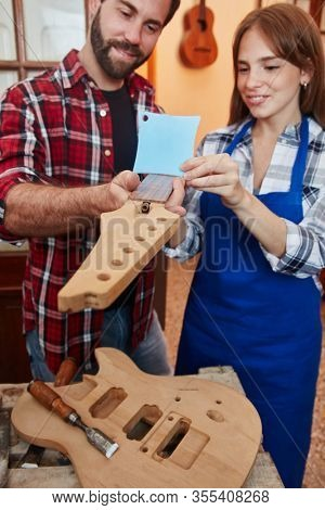 Guitar maker shows trainee radius knife in the workshop