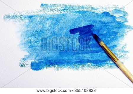 Watercolor Paper And Blue Watercolor Paint. Wet Watercolor Paper And Brush. Abstract Blue Background