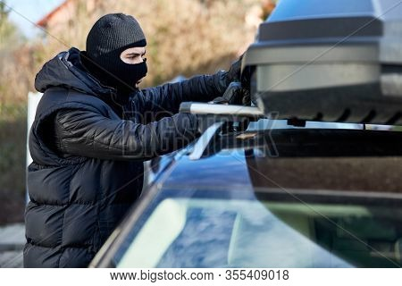 Thief opens roof box or roof rack on a car for theft