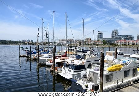 Yachts Moored In Marina In Victoria  Downtown. Inner Harbour On Bright Sunny Day, City Buildings In