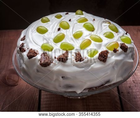 Celebratory Homemade Cake With Cream And Fruit On A Glass Cake, Close-up, Wooden Plank Table