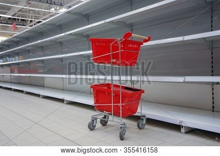 Shopping Trolley With Empty Baskets Against Empty Shelves In Grocery Store
