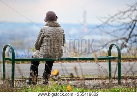 Old Woman Sitting On Bench In Autumn City Park. Lonely Widow Looking Deep At City, Self-reflection.