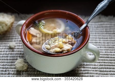 Delicious Homemade Chicken Broth Soup With Lemon Slice. Noodle Soup In Bowl And Breadcrumbs  On Tabl