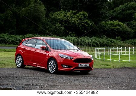 Scotland - April 1, 2019: A New And Shiny Red Ford Focus St Mark Iii Hatchback Car Parked In A Green