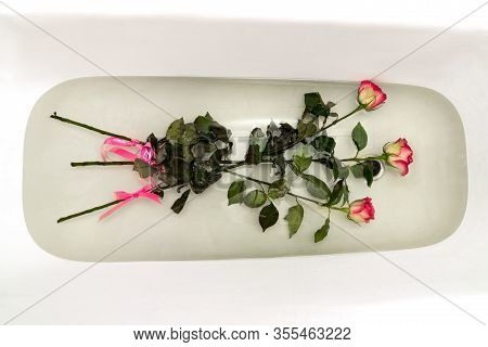 Bouquet Of Slightly Faded Roses Is Placed In The Bath To Revive The Flowers