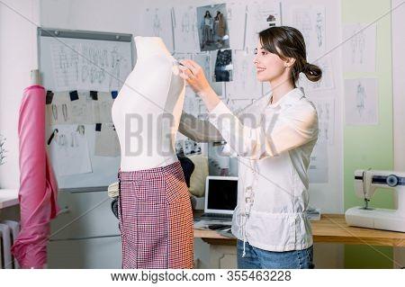 Female Dressmaker Working On New Model Tailoring Pants On Mannequin In Studio. Fashion Design Manneq