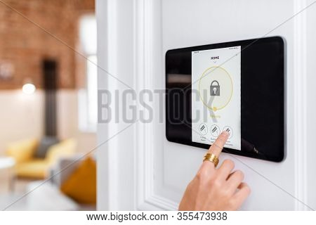 Controlling Home Alarm System With A Digital Touch Screen Panel Installed On The Wall. Concept Of Wi