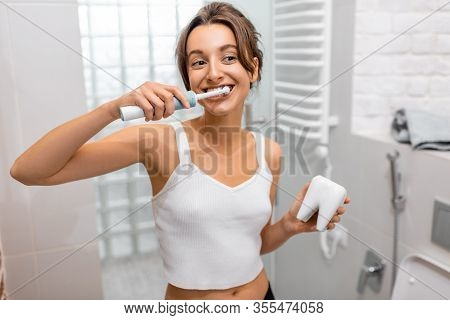 Young And Cheerful Woman Brushing Teeth With Electric Toothbrush During Morning Hygiene Procedures I