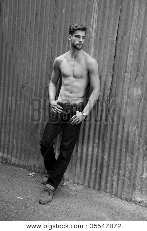 Outdoor photo of handsome, shirtless young man standing against grunge metal wall.