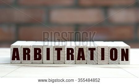 Concept Word Arbitration On Cubes Against The Background Of A Brick Wall