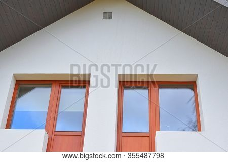 Part Of White House With New Eaves Made Of Wooden Planks And Brown Orange Windows With Copy Space On