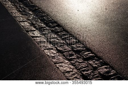 Tarmac Street With Gutter Of Cobblestones In Morning Sunlight After Rainy Night