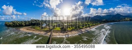 Aerial Panoramic Image Off The Coast Over Hanalei Bay And Pier On Hawaiian Island Of Kauai As The Su