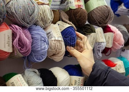 Minsk, Belarus - March 3, 2020: Close Up Of Yarn Balls. Girl Hand Choosing Yarn In Knitting Shop. Kn