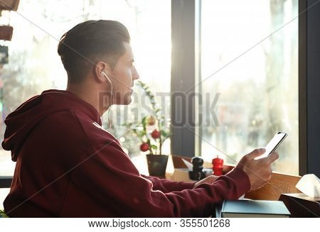 Man Listening To Audiobook At Table In Cafe