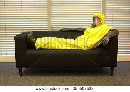 Quarantine - home arrest - man in professional in protective uniform lying on the sofa and waiting for the end