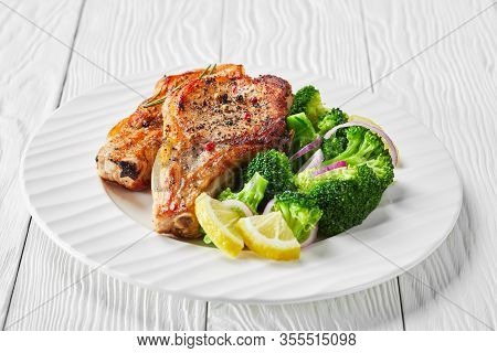 Close-up Of Broiled Pork Rib Chops With Lemon Wedges, Broccoli Salad On A White Plate On A Wooden Ta