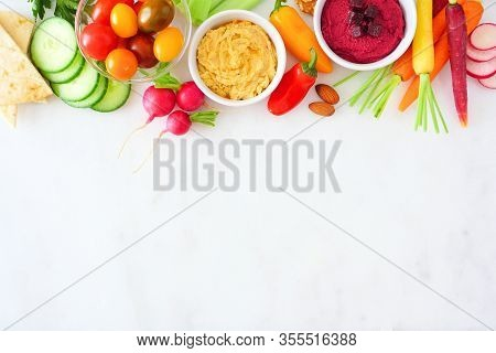 Assortment Of Fresh Vegetables And Hummus. Overhead View Top Border On A White Marble Background.