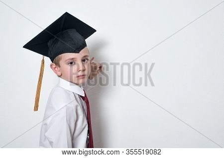 Sad Schoolboy In Academic Hat Writes On Board. Half-length Portrait On White Background Copy Space.