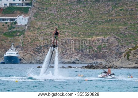 MYKONOS, GREECE - MAY 29, 2019: Man flying flyboarding on a Flyboard - hydroflighting device which supplies propulsion to drive the Flyboard invented by inventor Franky Zapata
