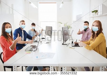 health, safety and pandemic concept - creative team wearing protective medical masks for protection from virus disease with computers showing thumbs up at office