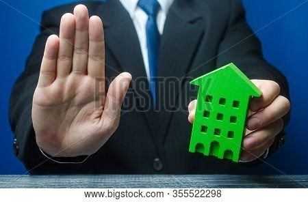 Man With A Green House Makes A Stop Gesture. Bank Refusal To Provide A Mortgage Loan. Housing Proble