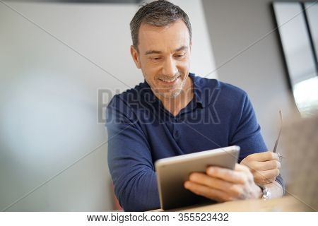 Portrait of middle-aged man connected on digital tablet