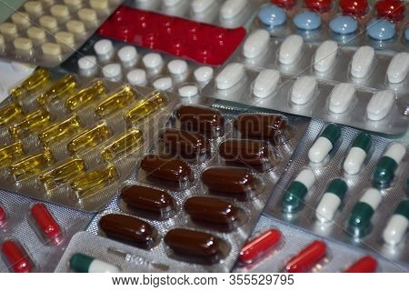 A Pile Of Pills In Blister Packs. Blister Packs Full Of Multi-colored Pills. Close-up On A Light Bac