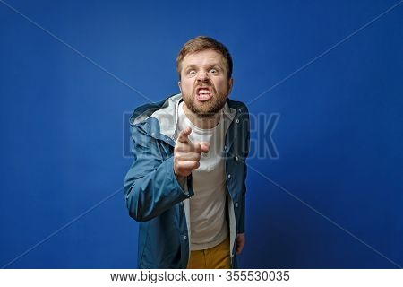 Angry Bearded Man Scandals With Someone, Pointing A Finger, Looks Furiously And Grins Teeth.