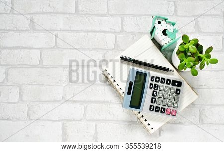 Top View Objects , Calculator, Black Pen On  Notebook  With Small Cactus Green Leave And Wooden Hous