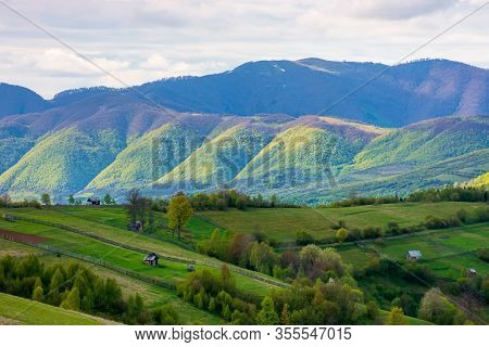 Rural Landscape In Mountains. Dappeled Light On Forested Hills. Wooden Fence Along The Hillside. Bea