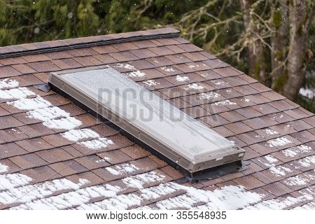 Sky Light Or Skylight Installed In A Roof On A Modern Home. Patches Of Snow Are Seen Near Skylight,