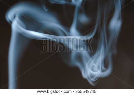 Wisps Of Smoke Float And Swirl Against A Dark Background.