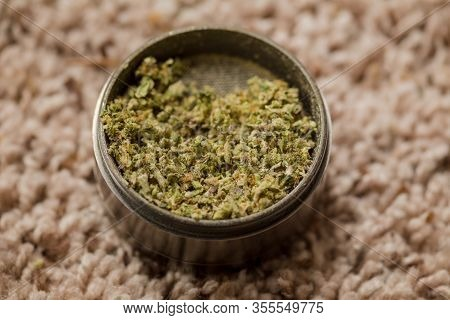 Close-up Details Of Ground Cannabis Flower In A Metal Grinder. Fresh And High-quality Green Buds In