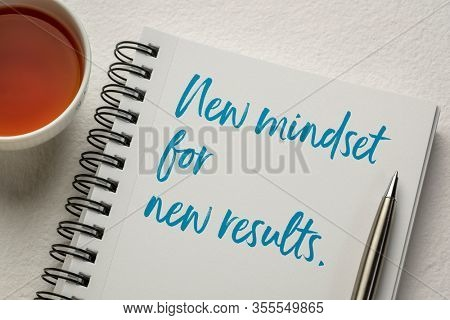 New mindset and new results concept - handwriting in a sketchbook with a cup of tea. Business, creativity and personal development.