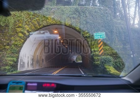 Perspective From Inside A Car As It Approaches A Tunnel. Sign Near Tunnel Says