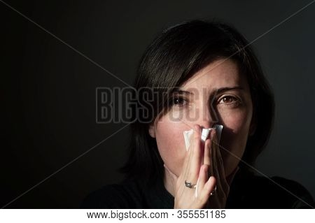 Portrait Of A Sick Brunette Woman Having Flu And High Fever, Sneezing Into Tissue On A Dark Backgrou