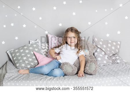 Favorite Toy. Girl Child Sit On Bed Hug Teddy Bear In Her Bedroom. Kid Prepare To Go To Bed. Pleasan