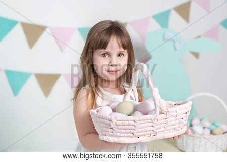 Easter! Beautiful Little Girl In A White Dress With A Basket With Multicolored Easter Eggs And Easte