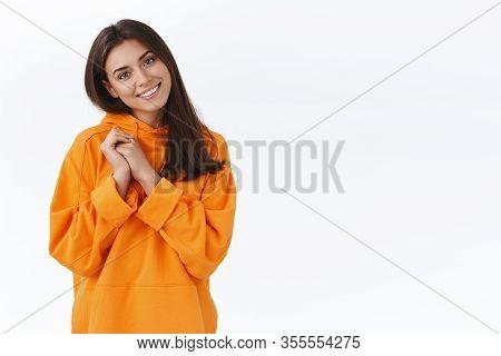 Tender Friendly-looking Feminine Brunette Girl In Orange Hoodie, Tilt Head And Smiling Pleasantly Ca