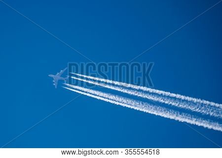 Airplane In The Sky With A Trace Of Steam Contrail. Airbus A380 Belonging To Etihad On The Route New
