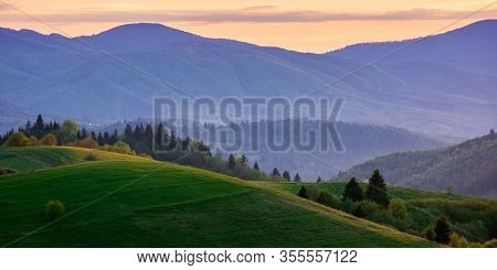 Panoramic Mountainous Countryside In Springtime At Dusk. Trees On The Rolling Hills. Ridge In The Di