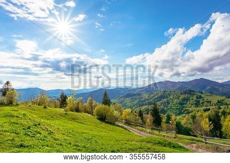 Stunning Rural Landscape In Mountains. Country Road Through Fields And Meadows On Hills Rolling In T